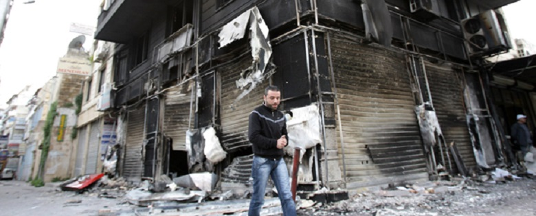 A man walks past a burnt-out building in