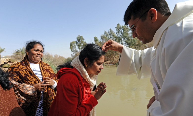 RELIGIOUS BROTHER SPRINKLES PILGRIM WITH WATER DURING MASS ALONG JORDAN RIVER IN WEST BANK