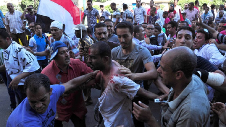 A wounded man is helped following clashes in Alexandria