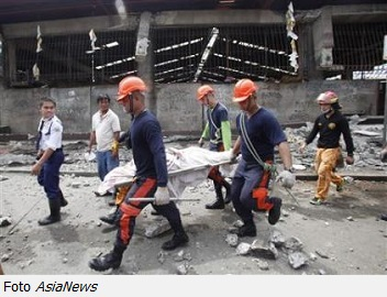 Rescue members recover the body of a vendor killed after an earthquake hit Pasil market in Cebu City
