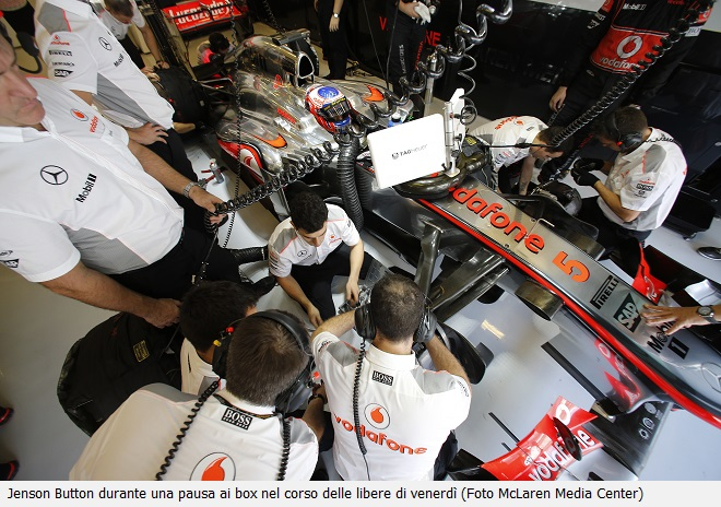 The team at work on the car of Jenson Button in the garage