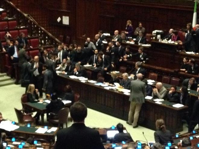 Bagarre alla Camera, con i deputati del M5S sui banchi del governo (foto da Twitter)