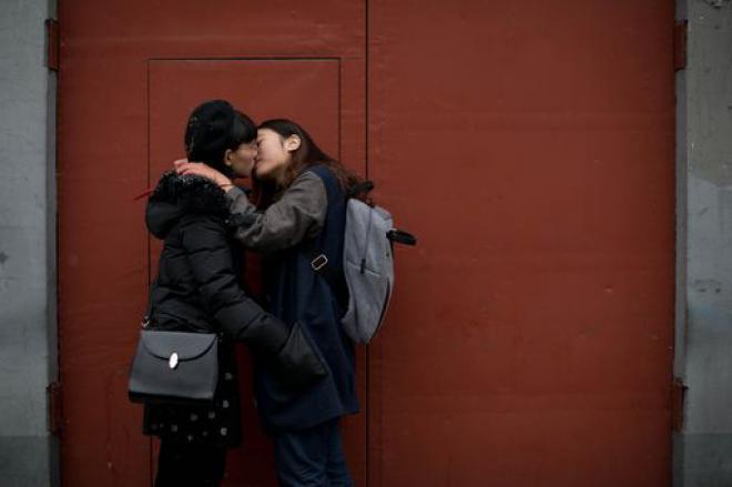 Due ragazze si baciano in pubblico a Pechino per manifestare contro la Russia - Foto TMNews