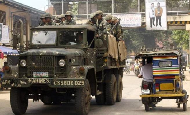 Soldati dell'esercito filippino ripresi mentre pattugliano le strade di Jolo, nelle Filippine Sud (foto Reuters)