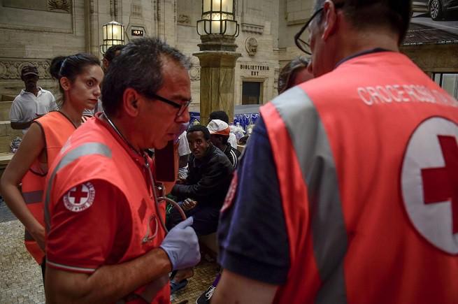 Personale della Croce Rossa Italiana nel mezzanino della Stazione Centrale di Milano (foto Adnkronos/AFP)
