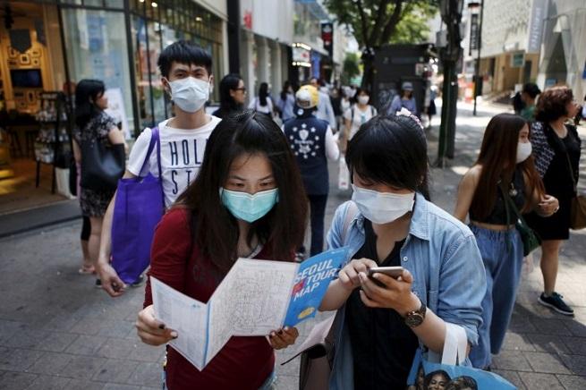 Turisti a Seul con mascherine al volto (usate da tutta la popolazione. Foto da Ibitimes.com)