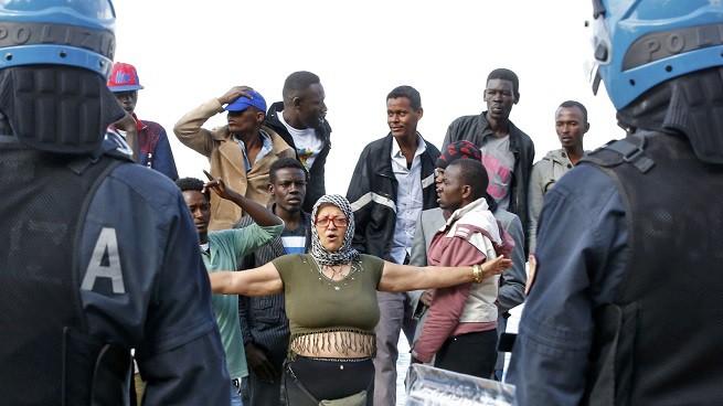 Un gruppo di migranti, in prevalenza provenienti da Eritrea e Sudan, fronteggiano agenti della Polizia di Stato costretti a sgomberarli dalla zona prospiciente il confine tra Italia e Francia a Ventimiglia (Foto REUTERS/Eric Gaillard via AGI)
