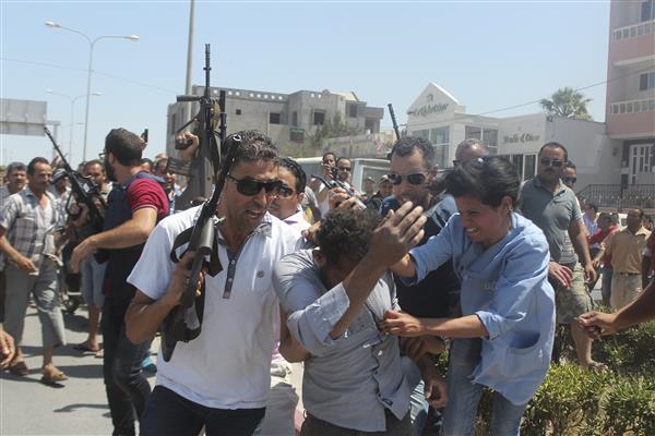Il sospetto terrorista sottratto a un possibile linciaggio della folla dalle forze di sicurezza tunisine, mentre una donna lo colpisce da sinistra (foto Reuters)